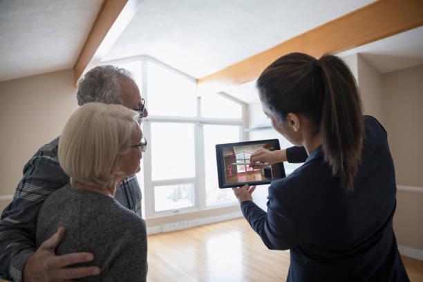 Une agent immobilier qui présente une maison à un couple de seniors