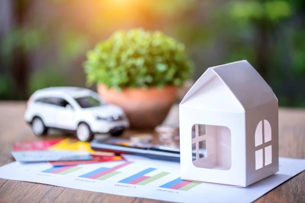 Maison en papier et petite voiture sur une table en bois