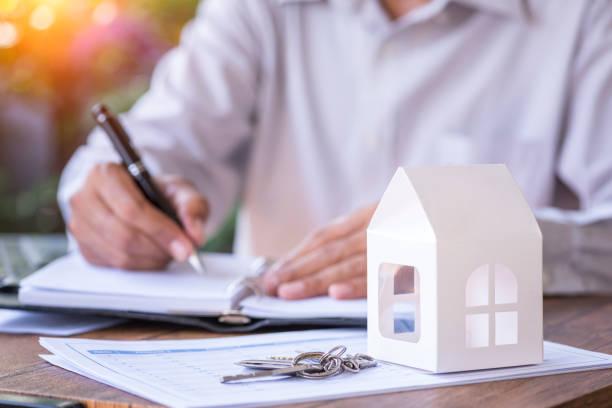 Personne qui signe un document avec une petite maquette de maison en papier et des clefs au premier plan