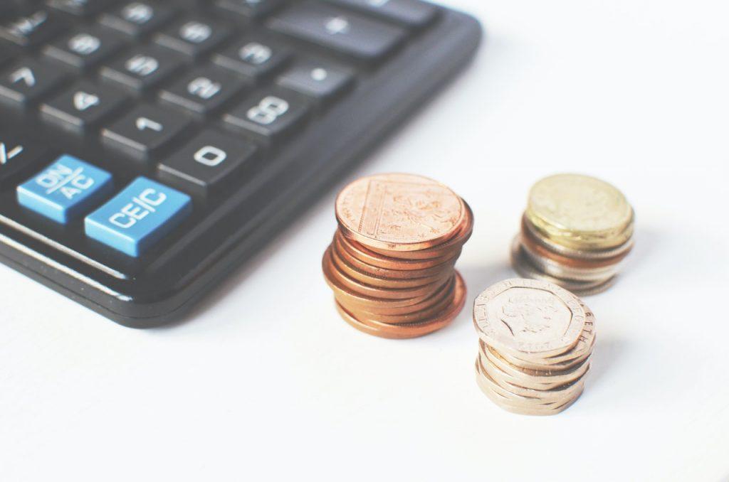 trois tas de pièces posés à côté d'une calculatrice